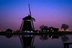 Typisk holländsk väderkvarn längs vattnet av en sjö under blå timme royaltyfria bilder