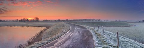 Typisk holländskt landskap med ett dike, i vinter på soluppgång royaltyfri fotografi