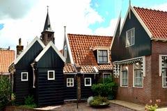 Typisk hus och kyrka i bakgrunden, Volendam, Holland Arkivfoto