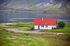 Typisk lantgårdhus på den isländska fjordkusten Arkivfoton