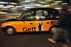 Typisk London taxi på gatorna av huvudstad för England ` s Arkivbilder