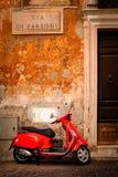 Typisk plats med en röd sparkcykel på en smal central Rome gata Royaltyfri Fotografi