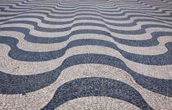 Typisk portugisisk kullerstentrottoar på gatan av Lissabon Royaltyfri Bild