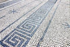 Typisk portugisiskt golv som göras av små stycken av den svartvita stenen royaltyfri fotografi