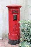 Typisk röd brittisk postbox isolerad gata Royaltyfri Foto