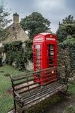 Typisk rött engelskt telefonbås i den Bibury byn Arkivfoton