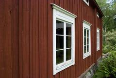 Typisk rött scandinavian trähus med vita fönster Arkivfoto