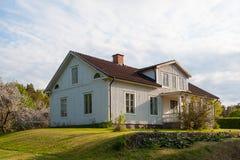 Typisk trähus som målas i ljus - grå färg, i Sverige Arkivfoto