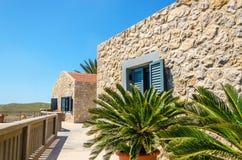 Typisk vägg för gamla grekiska byggnader med palmträd i foregrou Arkivbilder
