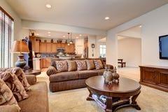 Typisk vardagsrum i amerikanhem med matta och sammetsof Arkivfoto