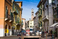 Typisk Verona gata med parkerade cyklar, Lamberti torn på bakgrund Royaltyfria Foton