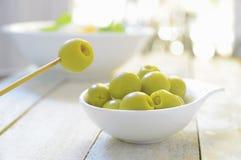 Typiska spanska tapas Några välfyllda oliv tjänade som på en platta på en vit trätabell Fotografering för Bildbyråer