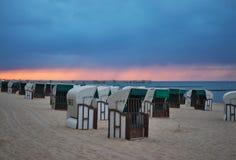 Typiska tyska korgar för strandstolar eller för strandstolar på stranden av Nord eller det baltiska havet i aftonen arkivbild