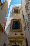 Typiska väggar av hus med blåa fönster och denskodde skyddsgallret fotografering för bildbyråer
