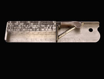 Typographer's composing stick. A composing stick with lead type against a black background royalty free stock image