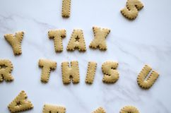 Small Biscuits Spelling `Tax This`. Typographic design biscuits spelling words on a Marble background royalty free stock images