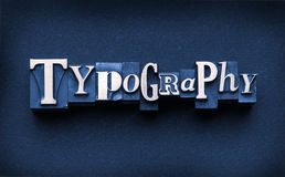 Typography. The word Typography done in letterpress type on a dark paper background and hand-tinted Stock Image