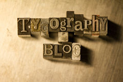 Typography blog - Metal letterpress lettering sign. Lead metal 'Typography blog' symbols text on wooden background Stock Photos