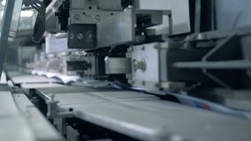 Typography machine moves books on a conveyor, automated production. 4K stock footage
