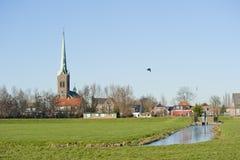 Typowa Holenderska wioski sceneria przeciw dajkowi Zdjęcie Stock
