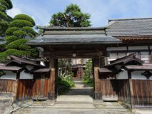 Typowa Japońska drewniana wejściowa brama otaczająca niektóre drzewami zdjęcia stock