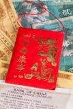 Typowa Porcelanowa czerwona koperta i różni banknoty Zdjęcia Stock