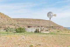 Typowa rolna scena z wodnym pompuje wiatraczkiem i tamą Zdjęcia Royalty Free
