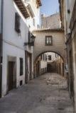 Typowa ulica światowego dziedzictwa miasto w Baeza, Uliczny Barbacana obok zegarowy wierza Obrazy Royalty Free