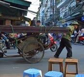 Typowa uliczna scena od Starej ćwiartki - mężczyzna ciągnięcia metal riksza pełno Wietnam, Hanoi - fotografia stock
