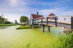Typowo tradycyjny holendera dom, wiatraczek, dziejowa architektura i most nad wodą przy Zaanse Schans, fotografia royalty free