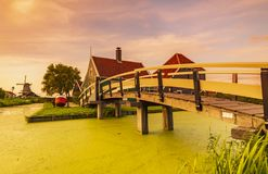 Typowo tradycyjny holendera dom, wiatraczek, dziejowa architektura i most nad wodą przy Zaanse Schans, zdjęcia stock