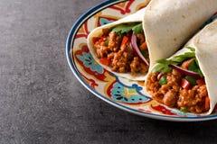 Typowy Meksykański burrito opakunek z wołowiną, frijoles i warzywami na czarnym tle, fotografia royalty free