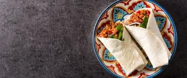 Typowy Meksykański burrito opakunek z wołowiną, frijoles i warzywami na czarnym tle, obraz royalty free