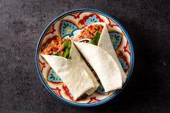 Typowy Meksykański burrito opakunek z wołowiną, frijoles i warzywami na czarnym tle, zdjęcia royalty free