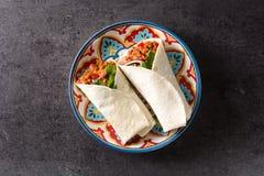 Typowy Meksykański burrito opakunek z wołowiną, frijoles i warzywami na czarnym tle, obrazy royalty free