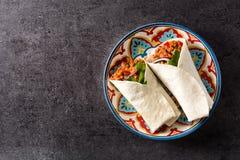 Typowy Meksykański burrito opakunek z wołowiną, frijoles i warzywami na czarnym tle, obraz stock