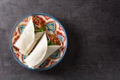 Typowy Meksykański burrito opakunek z wołowiną, frijoles i warzywami na czarnym tle, zdjęcia stock