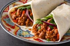 Typowy Meksyka?ski burrito opakunek z wo?owin?, frijoles i warzywami na czarnym tle, obrazy royalty free