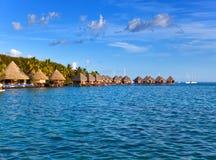 Typowy polinezyjczyka krajobraz - mali domy na wodzie przeciw niebieskiemu niebu Zdjęcie Stock