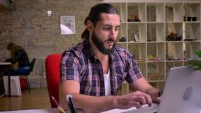 Typt de Kaukasische kerel van Nice met grote zwarte baard op toetsenbord terwijl het zijn bij zijn Desktop en dan het kijken met  stock video