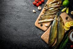 Typy uwędzona ryba z plasterkami wapno, cytryna, pomidory i ziele, fotografia royalty free