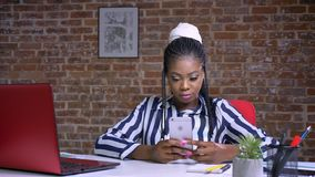 Typying afrykańska dziewczyna wyłaczał jej uwagę na smartphone chłodzącym podczas gdy siedzący przy stołem w studiu zbiory wideo