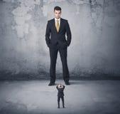 Tyrann des großen Geschäfts, der kleinen Mitarbeiter betrachtet Lizenzfreies Stockfoto