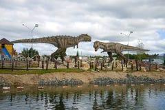 Tyrannosarie Rex och carnotaurus Skulpturer av rov- dinosaurier i barn`en s parkerar Arkivbild