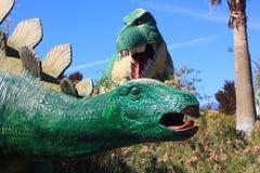 Tyrannosaure Rex et dinosaure de Stegosaurus à un parc Images stock