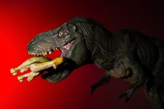 Tyrannosaurus biting a smaller dinosaur with spot light on the head and red light. On background Royalty Free Stock Photos