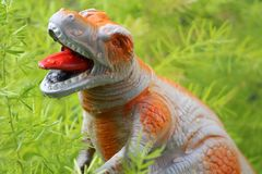 Tyrannosaurus rex toy among foliage. With open mouth and in position of attack Stock Photography