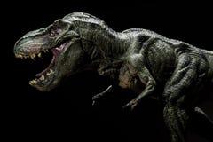 Tyrannosaurus toy on dark. Tyrannosaurus toy on a dark background close up Stock Images