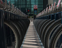 Tyre Alley. Two rows hire-cycles, neatly parked tyre-to-tyre at Canary Wharf, London Royalty Free Stock Photography