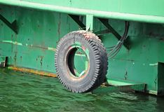 Tyre as fender on pier. Fender from old truck tyre on pier Royalty Free Stock Photo
